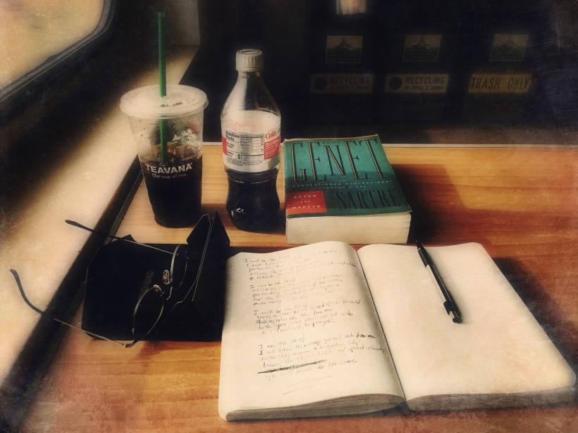 stylized photograph of a journal with pencil, a pair of eyeglasses, a copy of Jean-Paul Sartre's Saint Genet, a Starbucks cold drink cup, and a 20-oz. bottle of Diet Coke on a tabletop